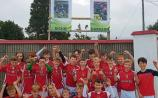 Doon under 12 hurlers pose beneath two posters dedicated to Darragh O'Donovan and Richie English